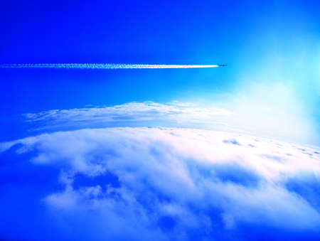 Airplane con trail above the clouds