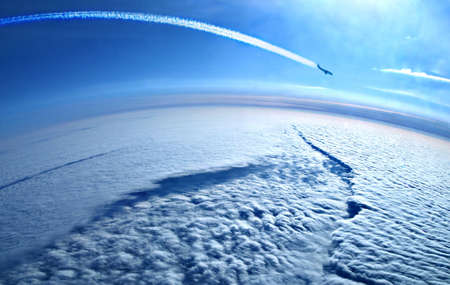 Airplane contrails in the blue sky above the clouds Stock Photo