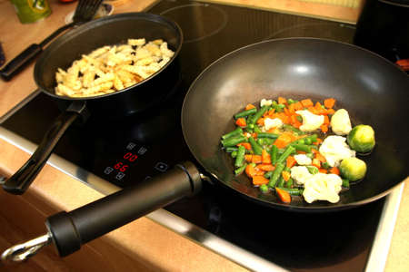 Preparing the meal - stir fry vegetables and potatoes in pan