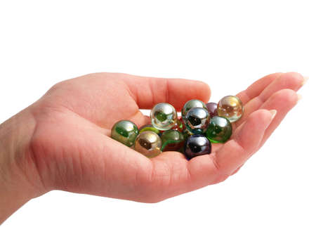 A womans hand holding colorful glass marbles