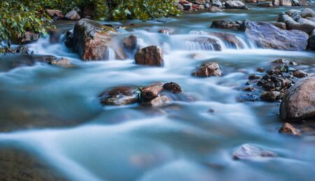 Mountain river concept. Clear river running fast, hitting rocks.