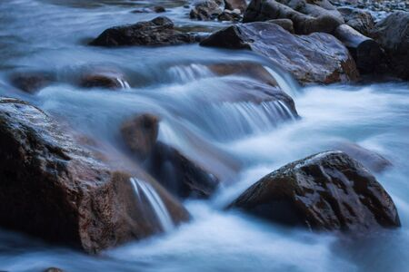 Raging mountain river running fast between small rocks and stones. Stock Photo