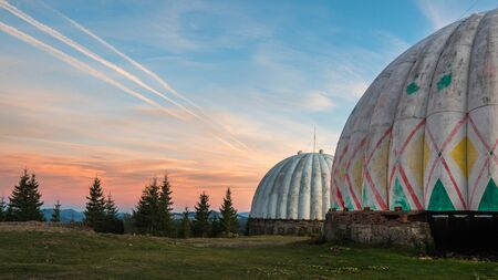 Unusual architecture concept. Dramatic sunrise over uniquely designed old radar station in shape of white spheres with red pattern. Reklamní fotografie