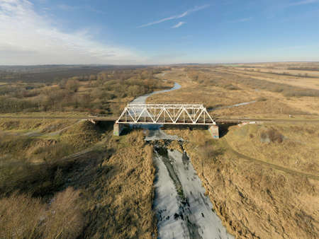 A railway bridge over a river covered with ice against a background of a flat landscape. Photo from the drone.