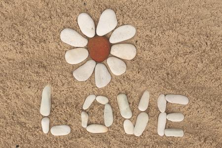 silhouette fleur: fleur de pierre, couché sur le sable. faite de cailloux blancs et rouges. pour les concepteurs et impression