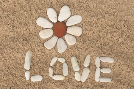 flower shape: flower stone, lying on the sand. made of white pebbles and red. for designers and print