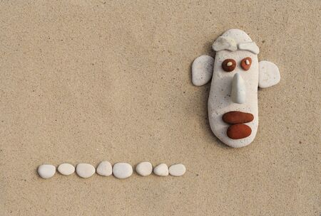 pebbles: the face of the pebbles on the sand. caricature and humor for greeting cards. Stock Photo
