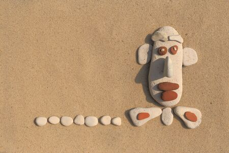 humor: the face of the pebbles on the sand. caricature and humor for greeting cards. Stock Photo