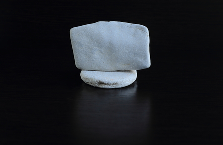 smooth stones: a set of smooth stones on a black background, stacked in the order