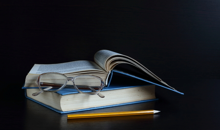 reading glasses: books lie on each other, near reading glasses. dark background Stock Photo