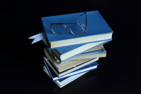 to lie: books lie on each other, near reading glasses. dark background Stock Photo