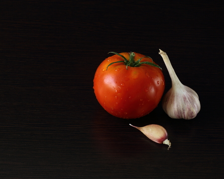 pungent: tasty and healthy food for your health bright and tasty tomatoes and pungent garlic on a dark background