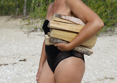 tourism and a healthy lifestyle, outdoors girl in swimsuit. stands and holds the firewood of birch