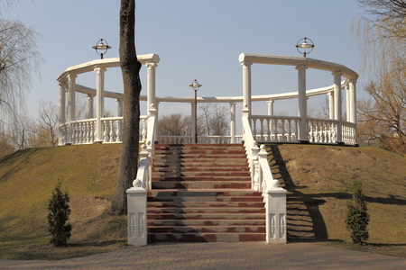 parapet: Openwork round arbor. White columns and stairs. Stands on a hill. Next tree.