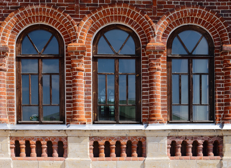 the wall of an old red brick building. There are three windows in the form of an arch.
