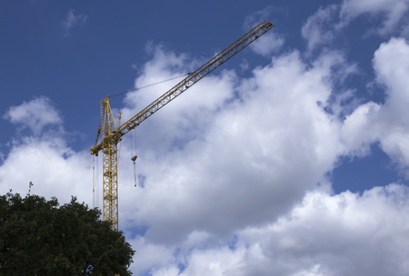 Construction crane against blue sky and clouds. In the left corner are trees.