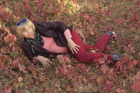 A happy middle-aged woman in the forest in early autumn. Pink clothes.Lies on the grass. There are large pink leaves around. Stok Fotoğraf