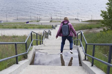 River embankment and high staircase. A woman is jumping through a puddle. A shot from the back high above the shore.