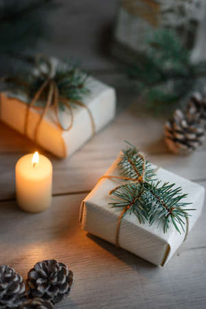 Boxes with Christmas presents on wooden surface against defocused lights