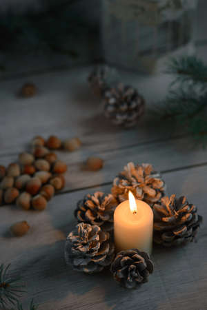 lighted: lighted candle, forest cones, hazelnuts on a wooden table, Stock Photo