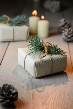 Christmas box on a wooden background with a candle and cones