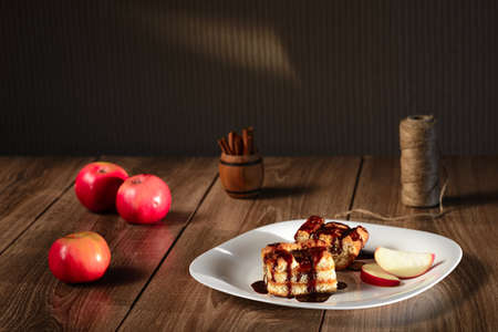 apple pie drizzled with chocolate on a white plate, wooden background, red apple, cinnamon