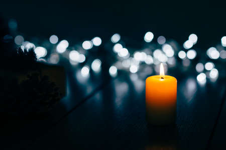 Burning candle on a table with Christmas decorations pine cones and a box on the background of garlands,