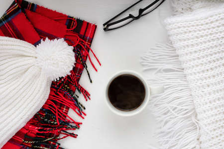 tog: Handmade knitted wool scarf and cap. Winter clothes. Hot coffee cup on wooden background. Concept cozy atmosphere with a cup of coffee in winter. Top view Stock Photo