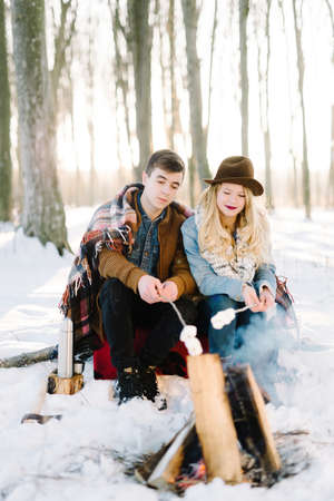 stylishly: hipster stylishly dressed young couple in a warm blanket, sit by the fire in the winter forest