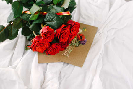 position d amour: a bouquet of red roses, envelope with congratulation on a background of linen good morning darling Banque d'images