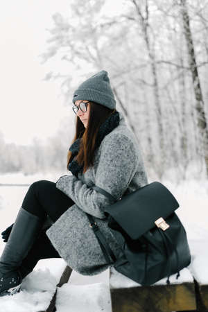 portrait of the brunette in glasses gray coat with a backpack
