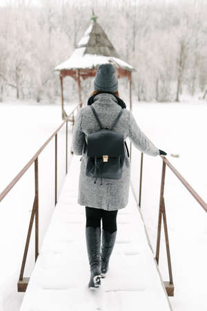 girl in a gray coat and a gray hat with a black backpack on a bridge in winter, rear view Stock Photo