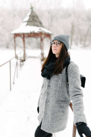 stylishly: girl in a gray coat and a gray hat in black glasses on the bridge in winter Stock Photo