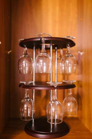 BARWARE: Glasses hanging upsidedown in wine bar interior Stock Photo
