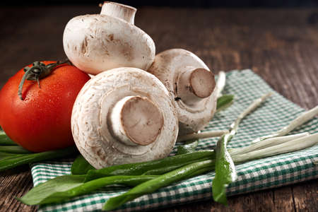 tomate de arbol: Mushrooms, tomato, greens on a napkin on an old wooden table Foto de archivo