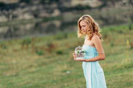 Light curly girl with a bouquet of wildflowers in a blue dress, a photo shoot in the spring on the nature