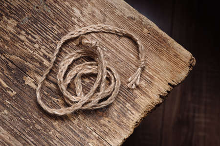 Woven rope on an old wooden table, decor Stock Photo