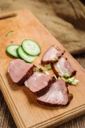 Close-up of sliced beef steak with cucumber on a cutting board on a wooden background, slices of fat Stock Photo