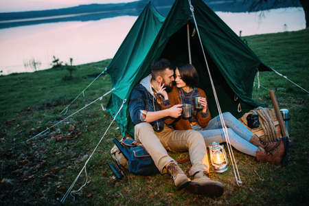 A man and a woman in a tent hold a flashlight at dawn near the lake, a picnic with an overnight stay
