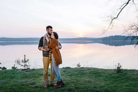 Man and woman lovers hold a flashlight at dawn near the lake, a picnic with a overnight stay