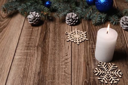 Still Life photo of a Christmas candle burning bright with large snowflakes and cones, copy space on a black background to add your own text. Stock Photo