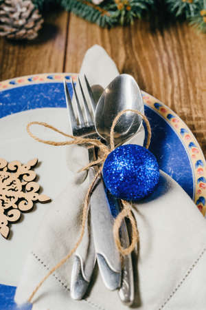 Christmas table, serving in blue tones, plate, napkin, appliance table on a wooden background with pine, cones and blue toys.