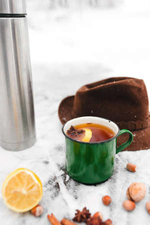 tea with lemon and cardamom in a green mug against the background of a snow-covered table