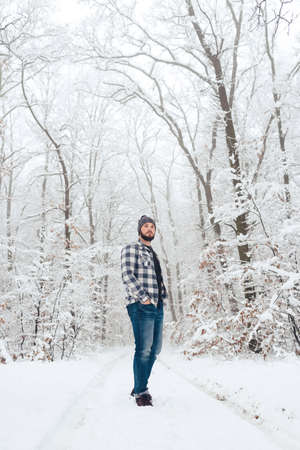 Handsome bearded man in a plaid shirt in the woods, in winter