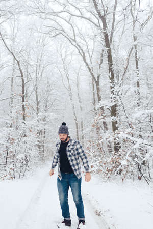 Beautiful Joyful, bearded man in a plaid shirt in the woods, in the winter, playing snowballs,