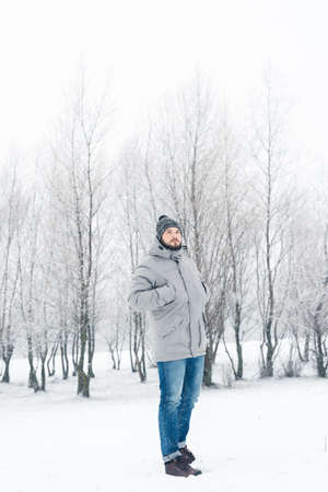 Outdoor portrait of a beautiful bearded man in a jacket and jeans. Casual winter fashion Stock Photo