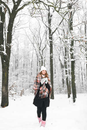 Beautiful young girl or woman on a walk in the forest, warms herself with hot tea, plaid in a cage, winter, cold Imagens