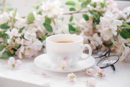 A coffee mug with a flowering branch and notes good morning on a blue country table from the top, breakfast on Mother's Day or on a woman's day