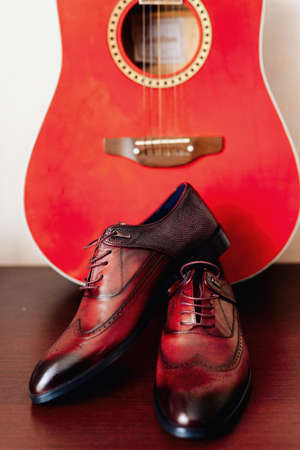 shoes of the groom on a background of red guitar, concept of vintage
