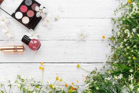 decorative cosmetics and wildflowers on a light wooden background